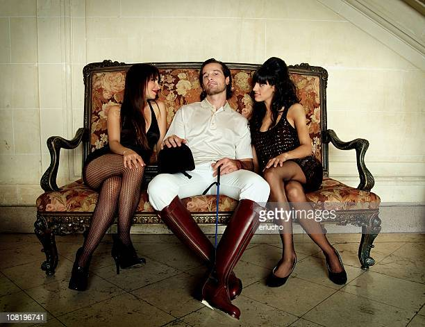 Male Polo Player Sitting on Couch with Two Young Women