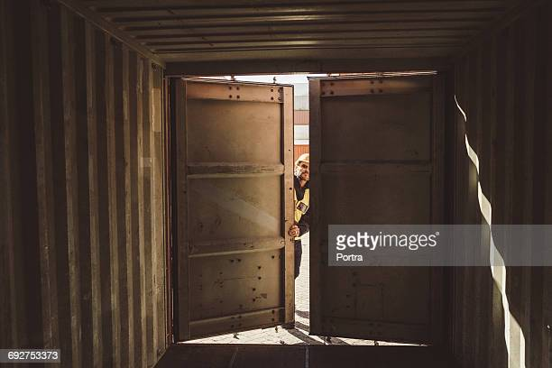 male port worker opening empty shipping container - container stock pictures, royalty-free photos & images
