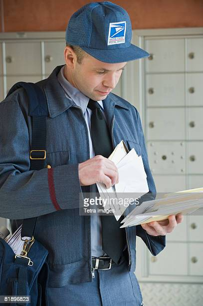 male postal worker looking at mail - post structure stock pictures, royalty-free photos & images