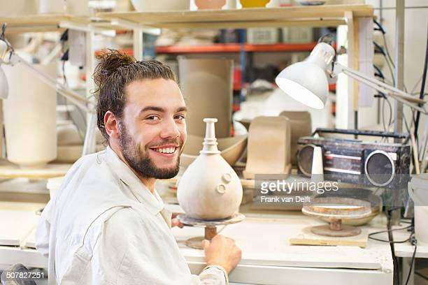 male potter working on vase in ceramic workshop - man bun stock pictures, royalty-free photos & images