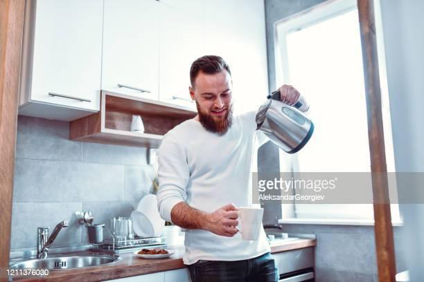 朝のコーヒーのカップに熱湯を注ぐ男性 - やかん ストックフォトと画像