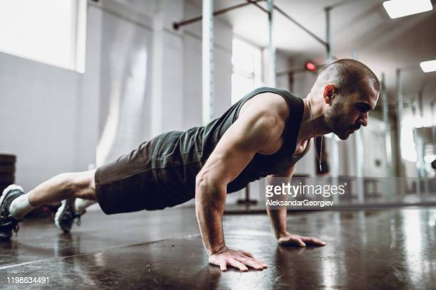 male practicing pushups in gym - push ups stock pictures, royalty-free photos & images