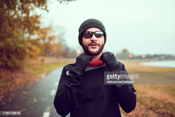 雨の秋の天候の間にジョギングセッションの準備をしている男性 - マフラー ストックフォトと画像