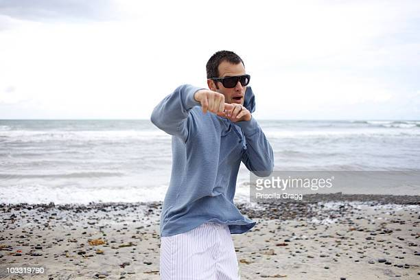 male pretends he is fighting at the beach. - rough housing stock photos and pictures
