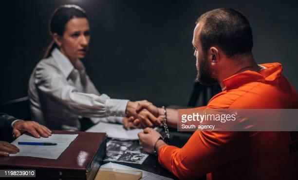 男性囚人は尋問室で女性弁護士と握手 - 執行猶予 ストックフォトと画像