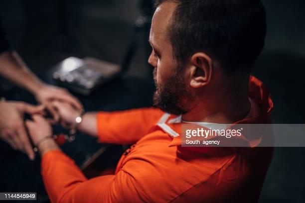 prisioneiro masculino que senta-se no quarto de interrogação - prisioneiro - fotografias e filmes do acervo