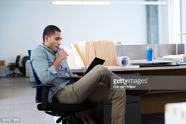Male profession looking at laptop  in office
