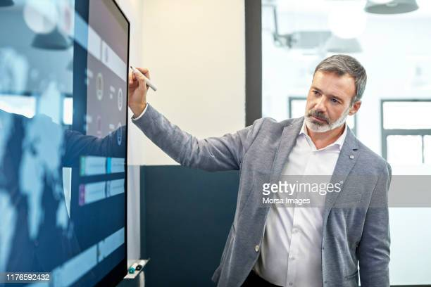 male professional looking at infographic on screen - business strategy stock pictures, royalty-free photos & images