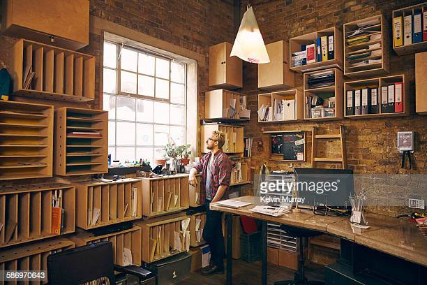 A male professional looks out of window in office