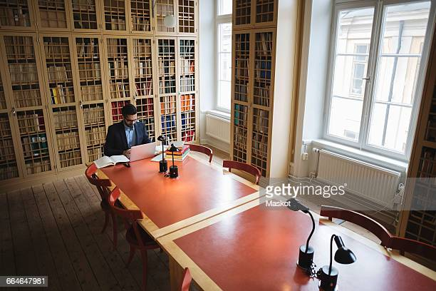 Male professional researching at table in law library