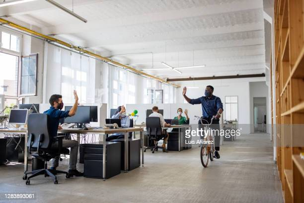 male professional riding cycle in creative office - arrival stock pictures, royalty-free photos & images
