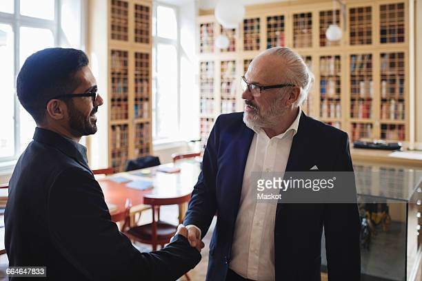 Male professional shaking hand with senior man in law library