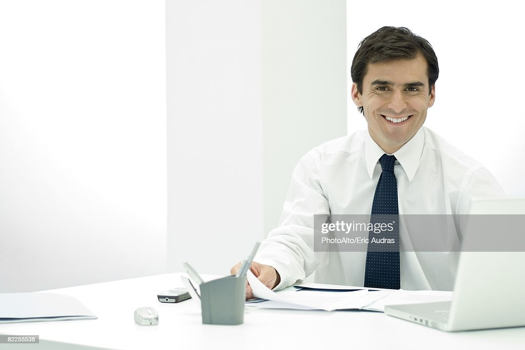 Male professional sitting at desk, smiling at camera : Stock Photo