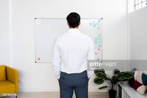 male professional standing in front of whiteboard while working in office - camisa blanca fotografías e imágenes de stock