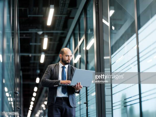 male professional using a laptop while standing - medium shot stock pictures, royalty-free photos & images