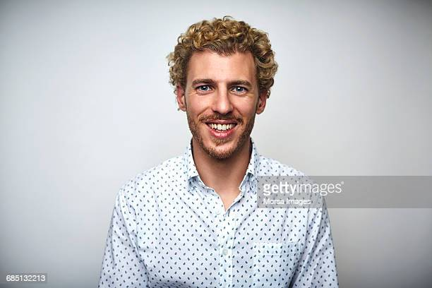 Male professional with curly hair over white