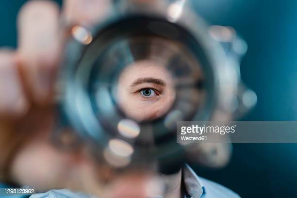 male professional's eyes seen through circular machine part in factory - image focus technique stock pictures, royalty-free photos & images