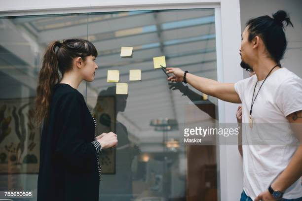 Male programmer explaining adhesive note to female colleague in office