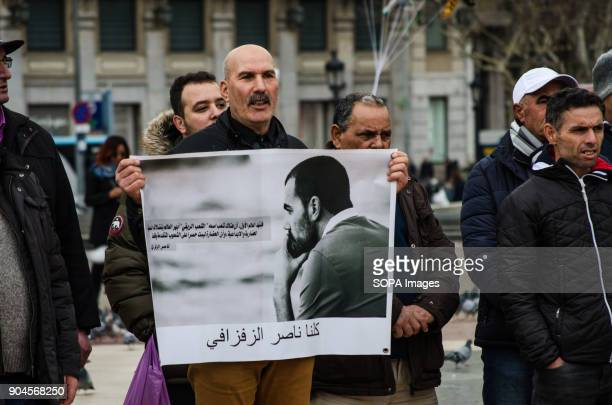 A male protester seen displaying a poster with the portrait of one of the people in prison Third March in Barcelona by the resistance freedom and...