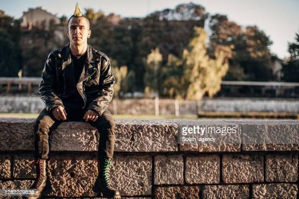 personne punk mâle dans des bottes de combat s'asseyant à l'extérieur dans la ville - punk photos et images de collection