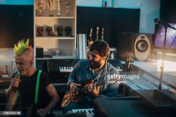 male punker singer and his guitarist in recording studio - punk music stock pictures, royalty-free photos & images