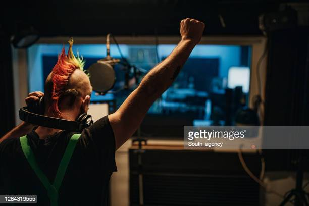 male punker singing into microphone in recording studio - punk music stock pictures, royalty-free photos & images