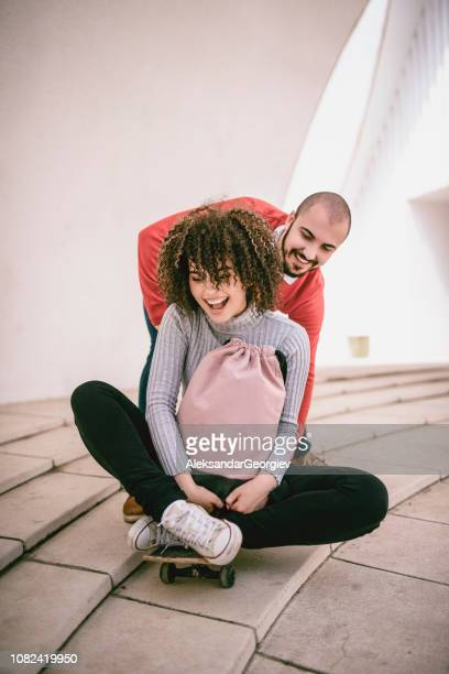 Male Pushing His Girlfriend While Sitting On a Skateboard