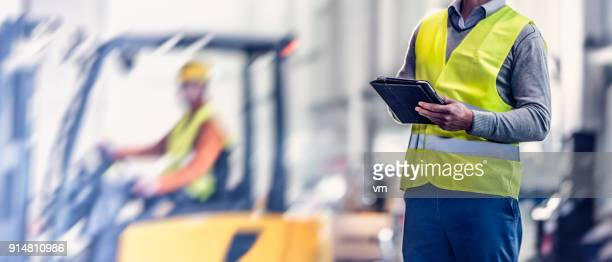 Male quality inspector with digital tablet in warehouse