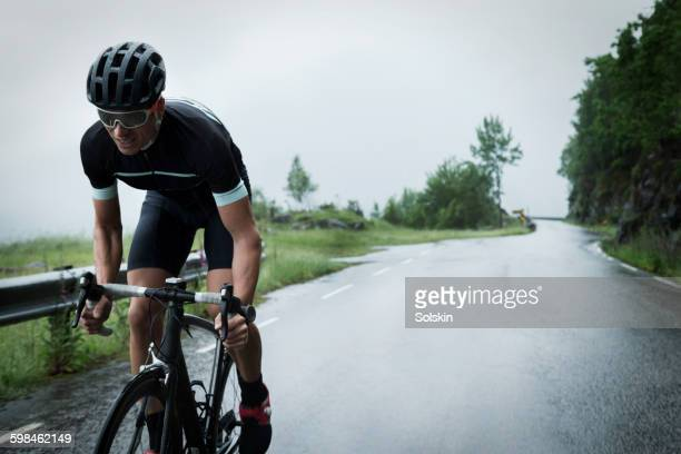 male race cyclist driving up mountain road - wielrennen stockfoto's en -beelden
