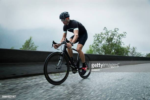 male race cyclist on mountain road - wielrennen stockfoto's en -beelden
