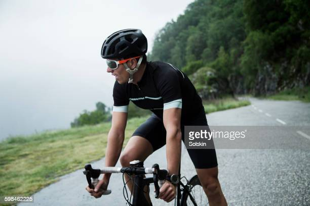 Male race cyclist resting by mountain road