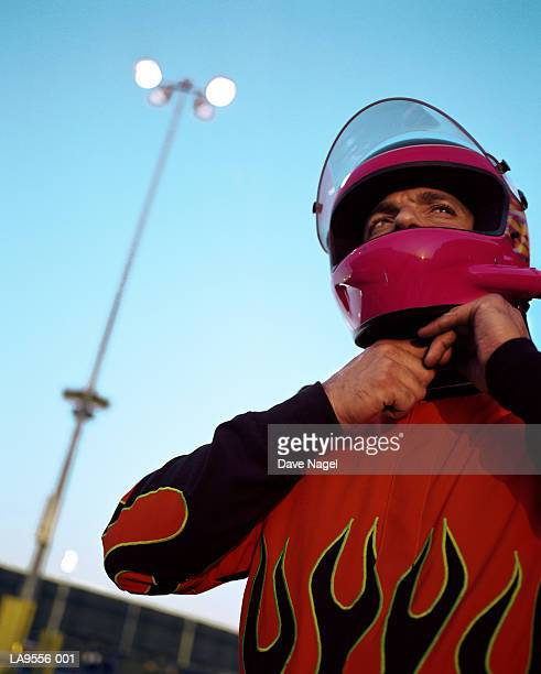 Male racing car driver suiting up for race