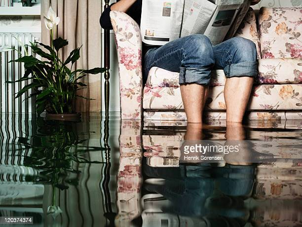 male reading newspaper in sofa in a flooded room