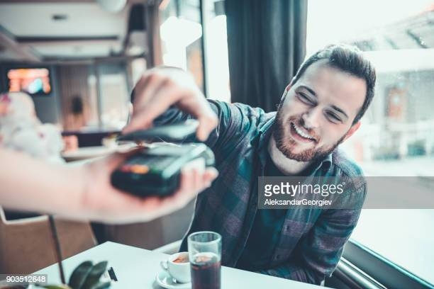 Male Receiving Bill and Paying With Credit Card In Cafe
