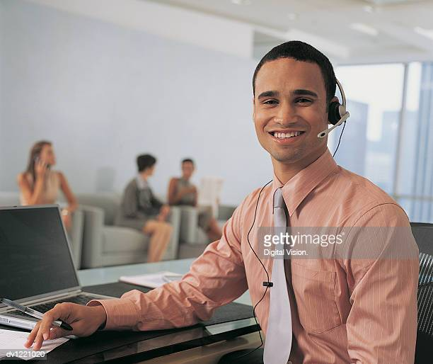 Male Receptionist Wearing Headset Sitting in Foreground, Three Businesswomen in the Background