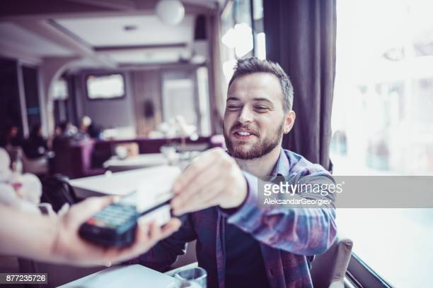 male reciving bill and paying with credit card in cafe - aleksandar georgiev stock photos and pictures