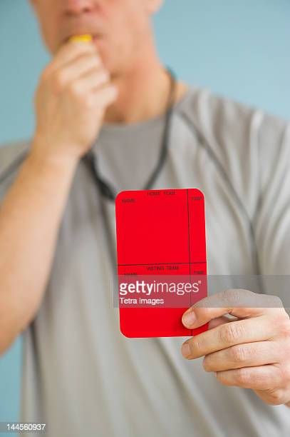 Male referee showing red card, studio shot