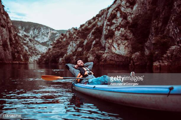 Male Relaxing In Kayak In The Middle Of Mountain Lake