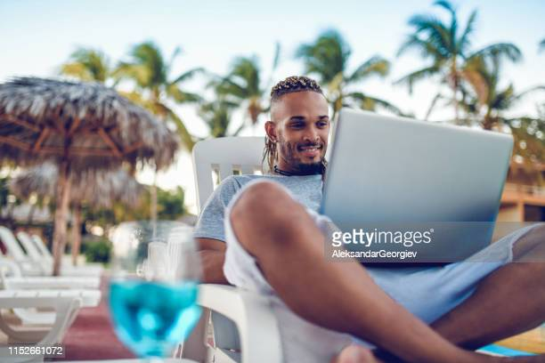 male relaxing with laptop and cocktail at resort - aleksandar georgiev stock photos and pictures