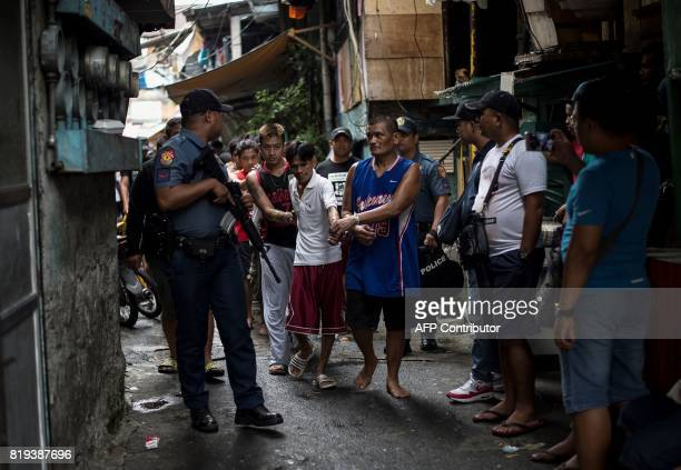 Male residents are rounded up for verification after police officers conducted a large scale antidrug raid at a slum community in Manila on July 20...