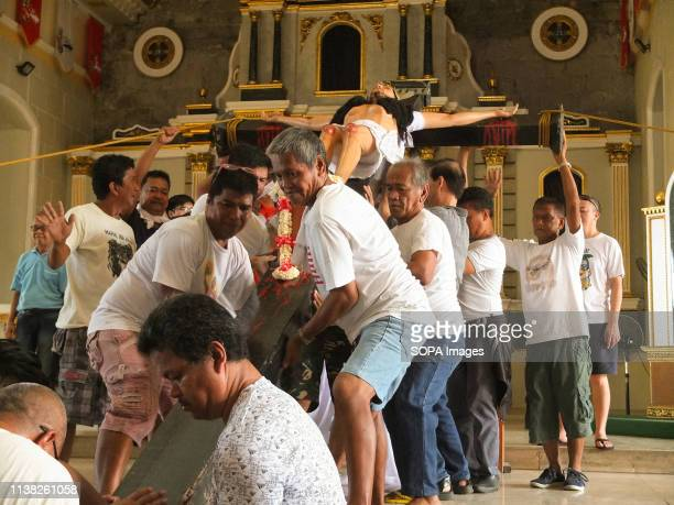 Male residents seen helping each other to stand the crucified Sto Entierro at the altar during Good Friday Every Good Friday the Malabon City town...