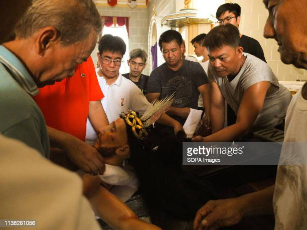 Male residents seen preparing the replica by putting white linen cloth during Good Friday Every Good Friday the Malabon City town folks especially...