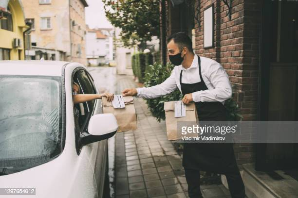 male restaurant employee delivers packed food to a female driver outside a restaurant. - curbside pickup stock pictures, royalty-free photos & images