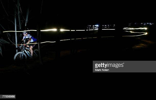 A male rider leaves a light trail as he makes his way through single track at night during the Mont 24 Hour MTB Race held at Majura Pines forest on...
