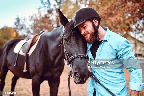 cavaleiro masculino que mostra o amor e a apreciação para seu animal favorito - evento equestre - fotografias e filmes do acervo
