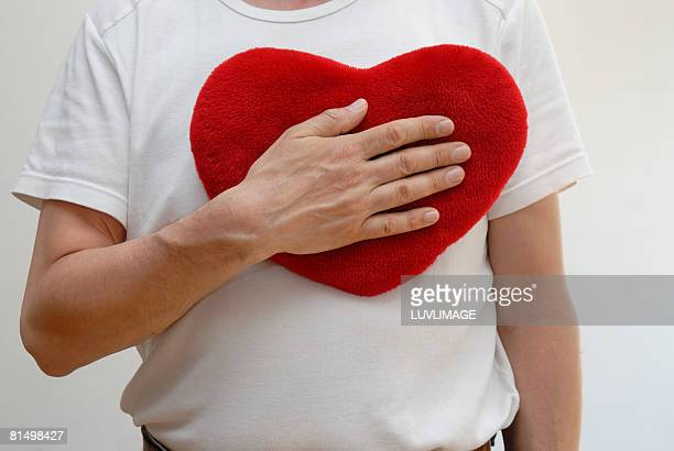male right hand holding heartshaped red cushion against his breast.