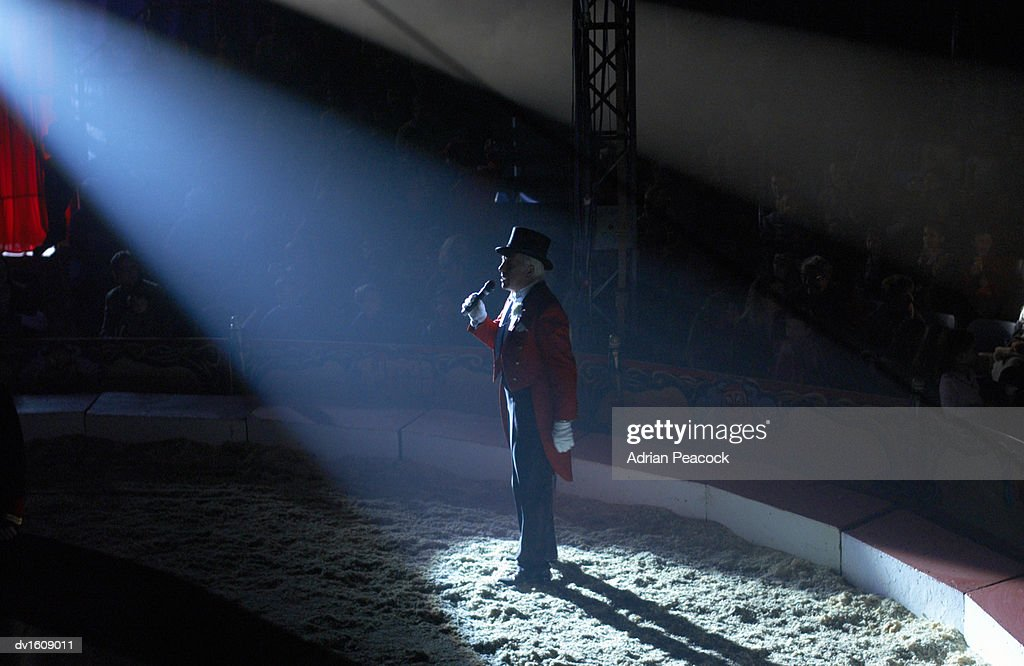 Male Ringmaster Stands in a Spot lit Circus Ring, Making an Announcement to the Audience : Stock Photo