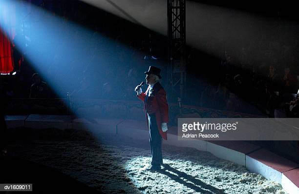 male ringmaster stands in a spot lit circus ring, making an announcement to the audience - personas en el fondo fotografías e imágenes de stock