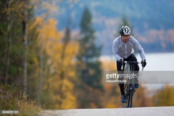 Eine männliche Radrennfahrer reitet auf einer ruhigen Landstraße in British Columbia, Kanada im Herbst.