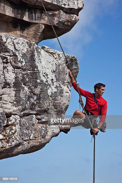Male rock climber abseiling down cliff face.